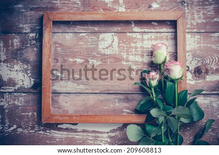 Bouquet of pink roses and a wooden frame on old board background, vintage color tinting - stock photo