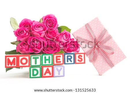 Bouquet of pink roses and pink gift next to wooden blocks of different colours spelling mothers day close up - stock photo