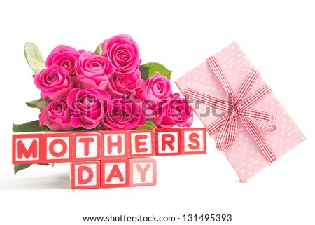 Bouquet of pink roses and pink gift next to wooden blocks spelling mothers day close up - stock photo