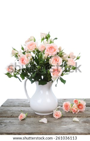 Bouquet of pink roses  in a vase on a wooden table - stock photo