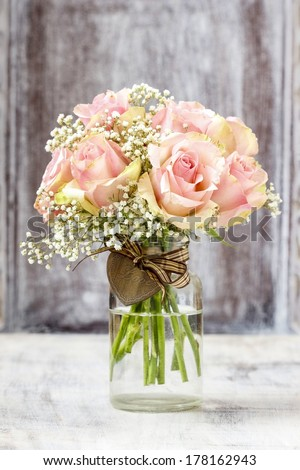Bouquet of pink roses in transparent glass vase.  - stock photo