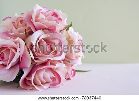 Bouquet of pink roses laying on a table. - stock photo