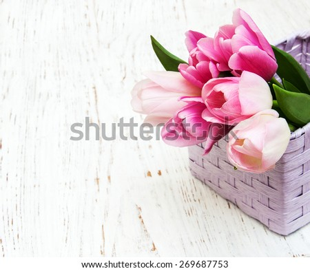 bouquet of pink tulips in a basket on a wooden background - stock photo
