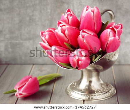 Bouquet of pink tulips in metal vase on wooden background - stock photo