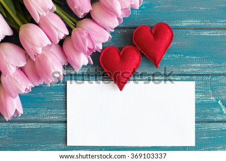 bouquet of pink tulips lie on texture painted in blue color table, next to a white envelope and two red handmade hearts  - stock photo