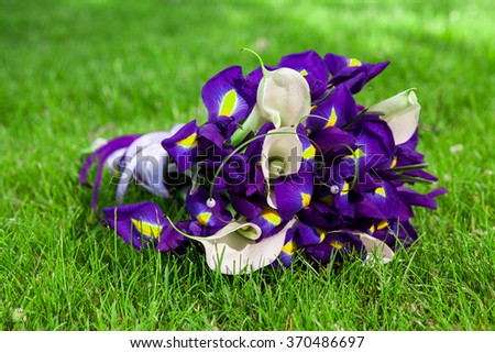 Bouquet of purple irises and white calla lilies in the grass - stock photo