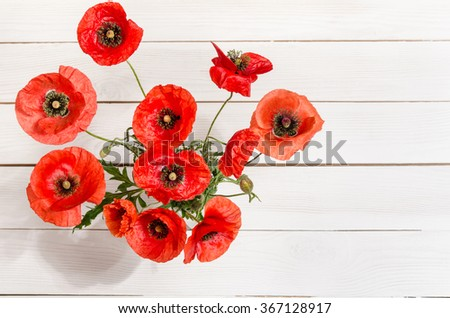 Bouquet of red poppies in glass vase on old white wooden table.top view - stock photo