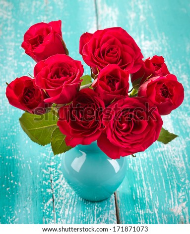 Bouquet of red roses in a vase on blue wooden background - stock photo