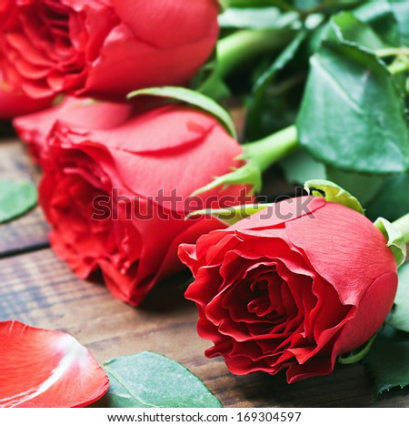 bouquet of red roses on the table. Focus on the rose in the foreground - stock photo