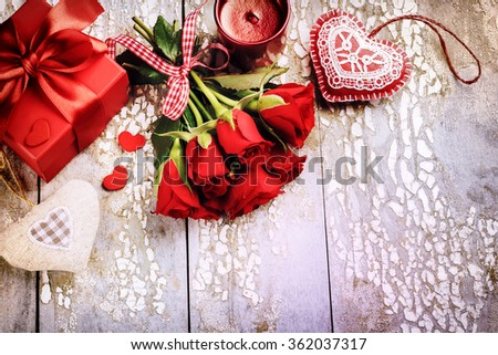 Bouquet of red roses with decorative hearts and presents. St Valentine's concept with copy space - stock photo