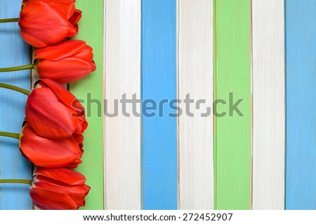 bouquet of red tulips and colorful wooden strips - stock photo