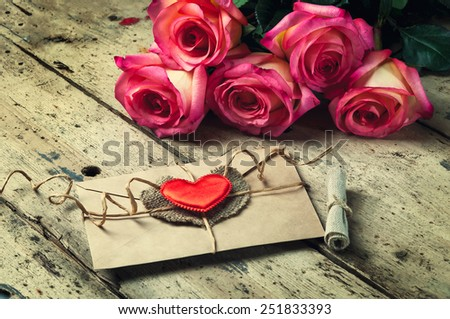 Bouquet of roses and an envelope with a love message  on  wooden background - stock photo