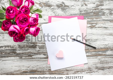 Bouquet of roses and blank paper sheets on old wooden table. Top view - stock photo