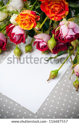 Bouquet of roses and white cardboard on a gray linen fabric closeup - stock photo