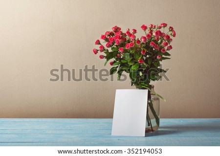 Bouquet of roses with a blank greeting card on a blue table in the background of the wall with copy space. Provence style - stock photo