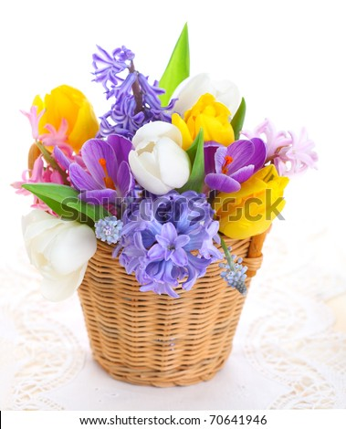 Bouquet of spring flowers in basket isolated on white background - stock photo