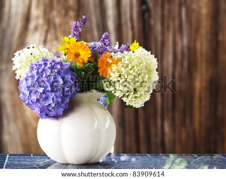 Bouquet of summer flowers in a vase before wooden background - stock photo