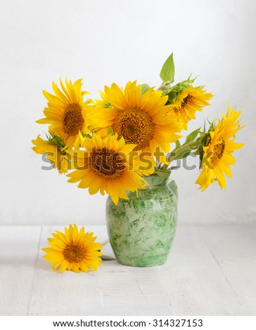 Bouquet of sunflowers in old ceramic jug on   wooden table. - stock photo