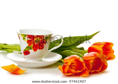 Bouquet of tulip flowers with cup of tea on white background - stock photo