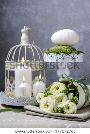 Bouquet of white ranunculus flowers (persian buttercup flowers) and easter table decoration with goose egg and white candles. - stock photo