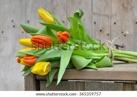 bouquet of yellow and orange tulips on a wooden box  - stock photo