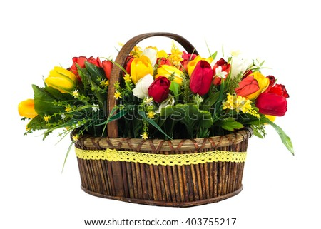 bouquet of yellow and red tulips with wildflowers in a wicker basket. Isolated on white background in studio - stock photo