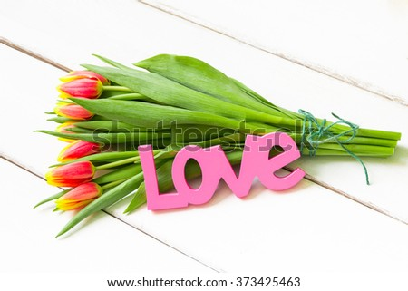 Bouquet of yellow red tulips on  wooden background with Love word. - stock photo