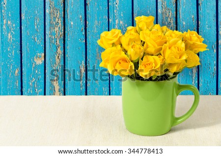 bouquet of yellow roses in a cup on a beige cotton - stock photo