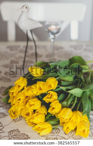 Bouquet of yellow tulips on a table with wooden figure on a background - stock photo