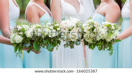 bouquets of roses in bride's hands - stock photo