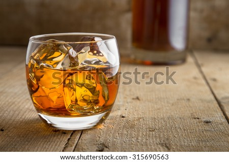 Bourbon brandy and bottle delicious tasty glass on ice classic modern rustic bar table bar saloon barrel - stock photo