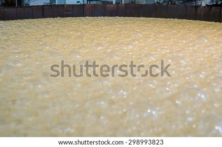 Bourbon in a mash tank bubbles as it ferments - stock photo