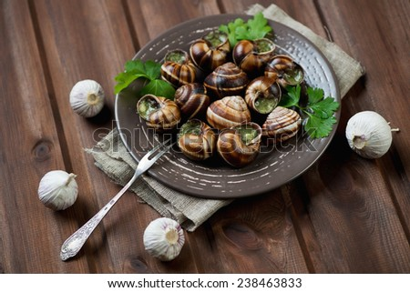 Bourgogne snails with garlic butter, rustic wooden background - stock photo