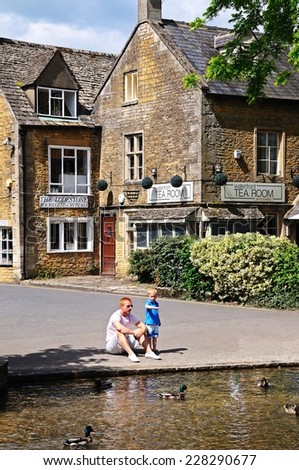 BOURTON ON THE WATER, UK - JUNE 12, 2014 - River Windrush with a father and son watching the ducks and tea-rooms to the rear, Bourton on the Water, Gloucestershire, England, UK, June 12, 2014. - stock photo