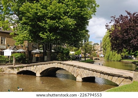 BOURTON ON THE WATER, UK - JUNE 12, 2014 - Stone footbridge across the River Windrush with tea-rooms to the left, Bourton on the Water, Gloucestershire, England, UK, Western Europe, June 12, 2014. - stock photo