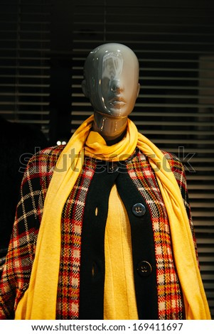 Boutique display window with mannequin in fashionable coat and neck scarf - stock photo