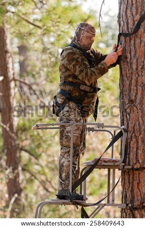 Bow hunter in a ladder style tree stand  - stock photo