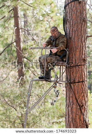Bow hunter in a ladder style tree stand demonstrating safe practices by using a safety harness and a haul line - stock photo