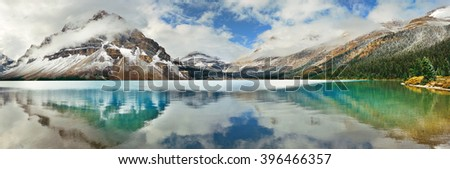 Bow Lake panorama reflection with snow capped mountain and forest in Banff National Park - stock photo