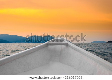 Bow  of a boat with sunset color view. - stock photo