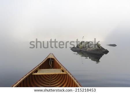Bow of a Cedar Canoe and Rocks on a Misty Morning - Haliburton, Ontario, Canada - stock photo