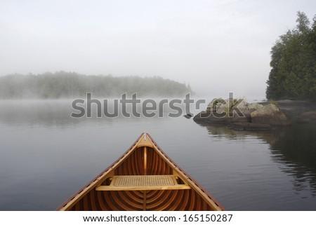 Bow of a Cedar Canoe on a Misty Lake - Ontario, Canada - stock photo