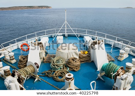 Bow of a Ferry Ship as it heads out to sea between two promontories of land. - stock photo