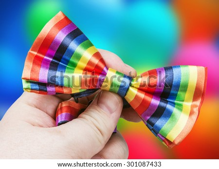 bow tie the colors of the rainbow in her hand against the background of balloons - stock photo