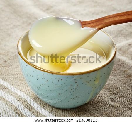 bowl and spoon of vanilla sauce - stock photo