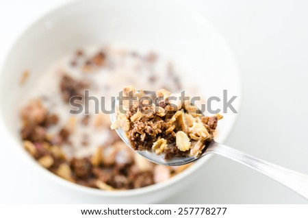 Bowl and spoon with breakfast cereals on white background - stock photo