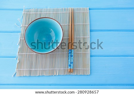 bowl for sushi and chopsticks on the Makis on a clean blue table - stock photo