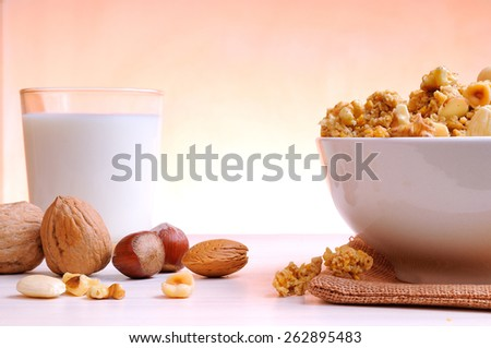 Bowl full of cereal with dried fruits and glass of milk at the bottom - stock photo