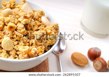 Bowl full of cereal with dried fruits and glass of milk at the bottom top view - stock photo