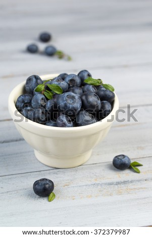 Bowl full of fresh blueberries on a wooden background - stock photo